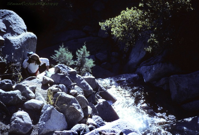 Kathy cllmbs along the creek