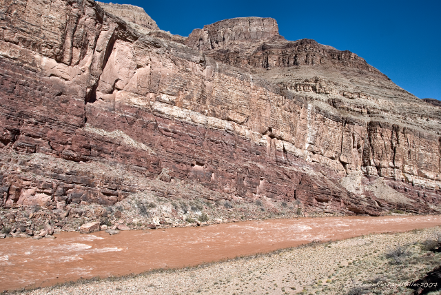 75 Mile Rapid, upstream view. 75 Mile has a few large holes randomly distributed throughout the middle and bottom of the rapid. Note the rapidly rising layers of the Shinumo Quartzite in the cliff on the opposite side of the river.