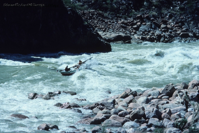 "In the high water of Sept. 1983, we coincided with a film crew that was re-enacting Powell's trips of exploration. The movie they produced is now shown at the theater in Tusayan. Accompanying that trip was the well-known conservationist and dory boatman Martin Litton. We were scouting from the bluff together, and Martin was accompanied by a dory guide who I believe was his son-in-law. The guide offered Martin a hard hat, to which Martin replied: ""I'm not going to wear that damn thing."" The guide, seen in the back of the dory, wore his."