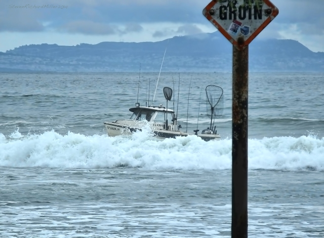 A fishing boat navigates the surf at the mouth of the tidal river