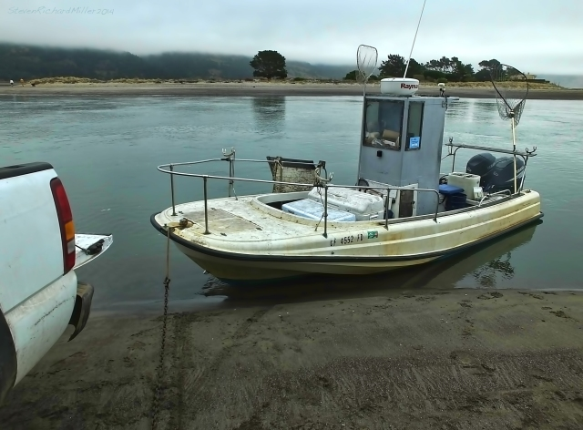 A fishing boat comes to shore alongside the town of Bolinas to offload fish and equipment