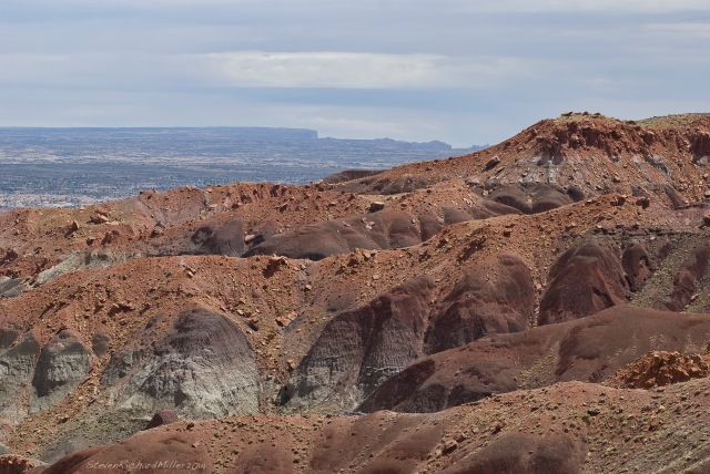 View to the east at Clay Hills Pass. Muley Point and Cedar Mesa are seen on the far horizon.