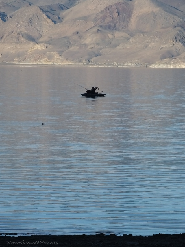 A lone pontoon-borne fisherman holds a trout aloft.