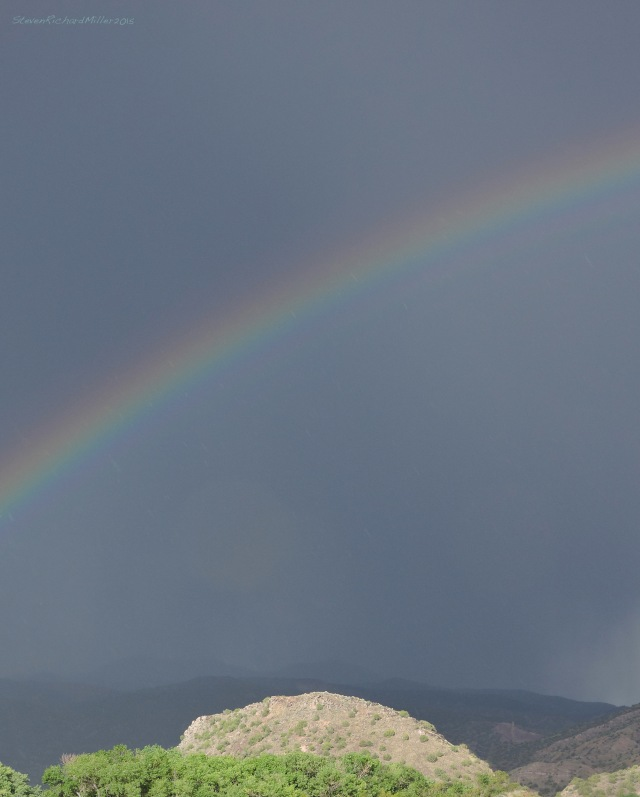 Rainbow, hill and Picuris Mountains, view to the east from our place alongside the Rio Grande