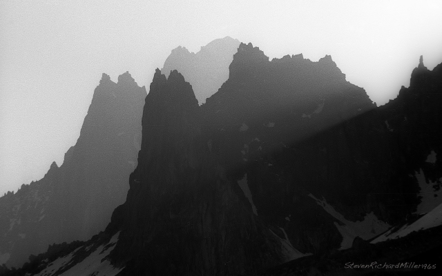 Telephoto shot from Plan des Aiguilles, with the Aiguille de L'M (left) and Petit Charmoz (right) in the foreground and the Drus (left) and the Aiguile Verte (right) in the background