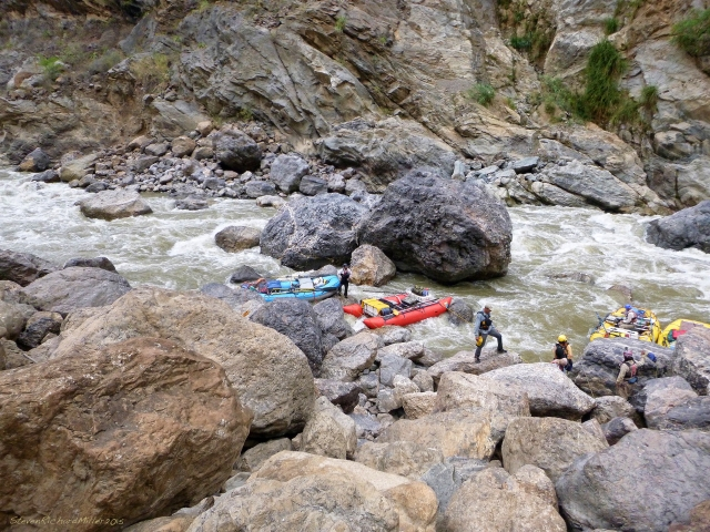The boats are collected along the river right shoreline, to the side of the group of boulders mentioned above