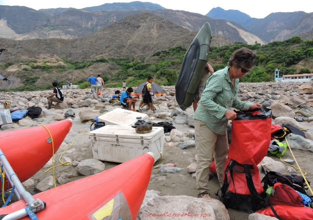 Chagual. Kathy re-packs her bag. Behind her, Karl hoists his packraft, while the local kids keep an eye on our doings.