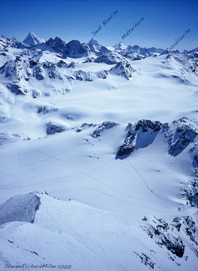 Skiers are seen on the Haute Route, heading out across the Glacier de Grand Desert, in the direction of Rosablanche, the low peak at the far side of the vast glaciated basin