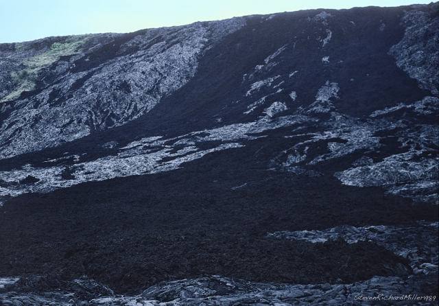 The top of the cliff, with lighter, pahoehoe flows, and darker aa flows